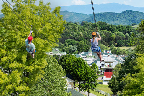 Two people zip down ziplines at Adventure Park Zip Lines in Sevierville, Tennessee, where guests staying at Xplorie participating properties can enjoy a free admission.