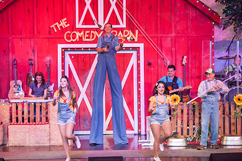 A silly performer on stilts juggles while the rest of the cast sings at The Comedy Barn Theater in Pigeon Forge Tennessee, where guests staying at Xplorie participating properties can enjoy a free admission.