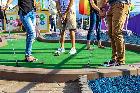 A group of four people playing a round of mini golf at Crave Golf Club in Pigeon Forge, Tennessee, which is available for free to guests staying at Xplorie participating properties.