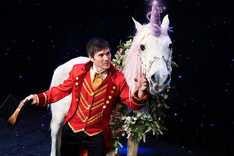 The amazing Darren Romeo poses with a unicorn while preforming at his magic show in Pigeon Forge, Tennessee, which is available for free to guests staying at Xplorie participating properties.