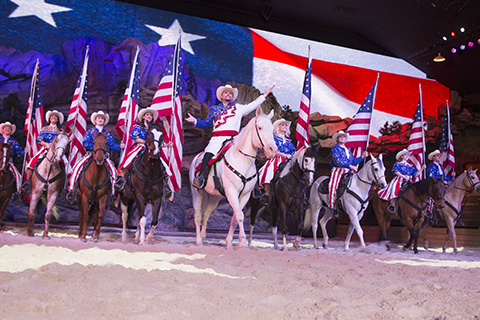 A group of performers on horseback sing during Dolly Parton's Stampede Dinner Attraction in Pigeon Forge, Tennessee, where guests staying at Xplorie participating properties can enjoy a free admission.