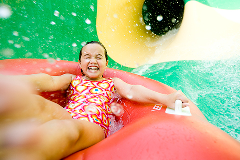 A little girl splashing down a water slide at Dollywood's Splash Country Water Park in Pigeon Forge, Tennessee, where guests staying at Xplorie participating properties can enjoy a free one-day ticket.