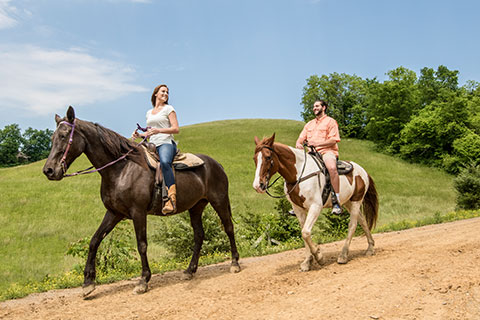 A young couple enjoys a relaxing horseback ride from Five Oaks Riding Stables in Sevierville, Tennessee, which is available for free to guests staying at Xplorie participating properties.