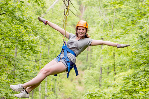A woman holds her arms out and grins while ziplining with Legacy Mountain Zip Lines in Sevierville, Tennessee, which is available for free to guests staying at Xplorie participating properties.