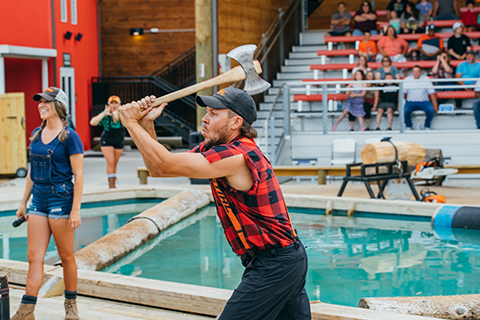 A lumberjack performing at Paula Deen's Lumberjack Feud Show in Pigeon Forge, Tennessee, prepares to throw an axe at a target. Guests staying at Xplorie participating properties can enjoy one free admission to this amazing show!