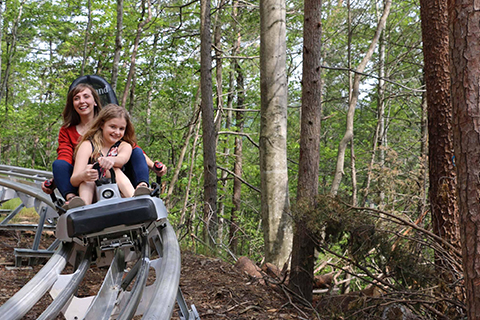 A mother and daughter zip along the Alpine Coaster at Rowdy Bear Mountain in Gatlinburg, Tennessee, where guests staying at Xplorie participating properties can enjoy a free admission.