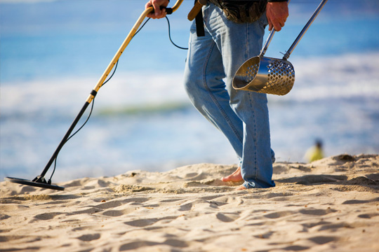 Searching for treasure with a metal detector rental from Beach Blast Rentals
